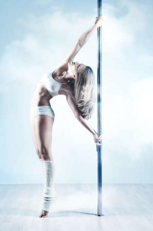 poledance: Young slim pole dance woman  Soft blue and white colors