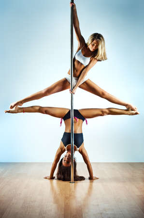 Two young slim pole dance women  photo