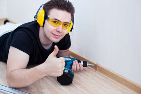 drill floor: Man worker installing plinth on balcony  Stock Photo
