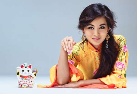 maneki: Young japanese woman with maneki neko cat