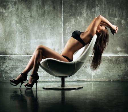 mujer desnuda sentada: Mujer sexy joven sentado en silla Foto de archivo