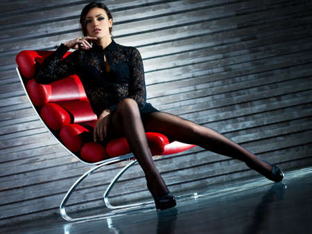 Young sexy woman sitting on chair  Camera angle view