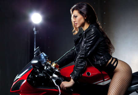 Young sexy woman sitting on motorcycle