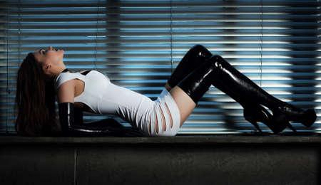 Young slim goth woman  On window background  版權商用圖片