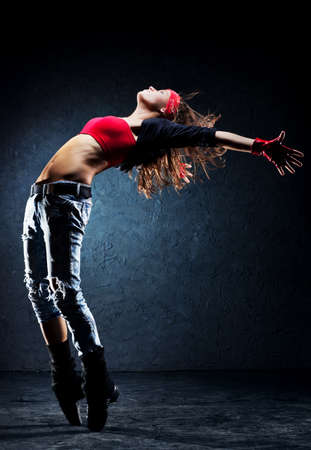 Young woman dancer  On wall background
