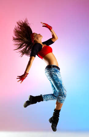 Young woman dancer jumping  On blue and pink background  photo