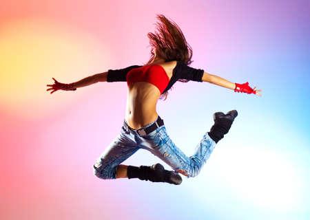 Junge Frau Tänzerin springen auf blauen und rosa Hintergrund