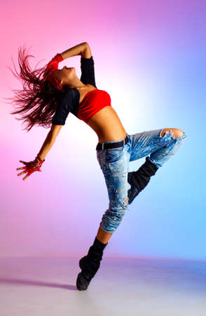 red jeans: Young woman dancer  On blue and pink background