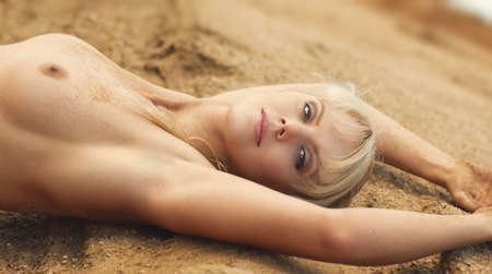 Young nude woman resting on sand. Stock Photo - 16937697
