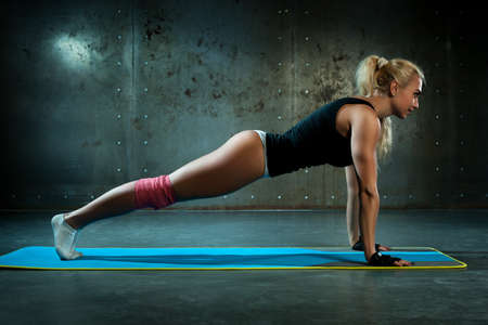 Young sexy fitness woman doing push-ups  Stok Fotoğraf
