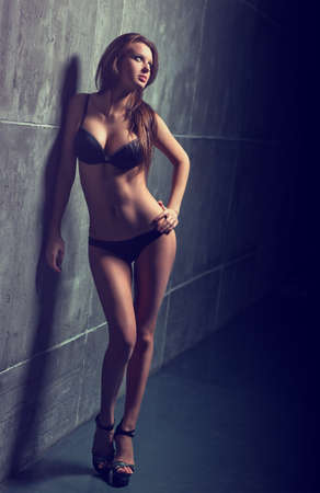 Young sexy woman standing at the wall. Stock Photo - 17625911