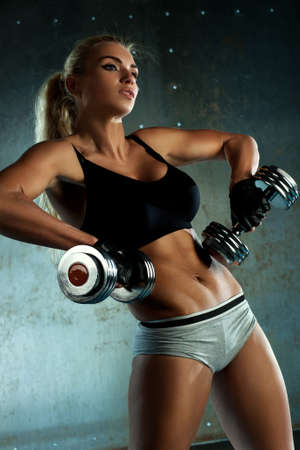 Young sports woman dumbbells exercises