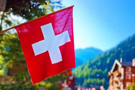 switzerland: Swiss flag on town background  Stock Photo