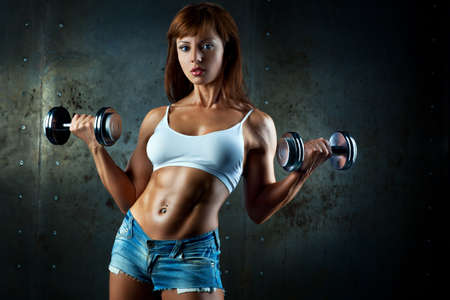 Young sports woman with dumbbells Stock Photo - 19287176