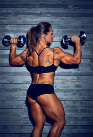 healthy body: Woman bodybuilder with dumbbells backside view