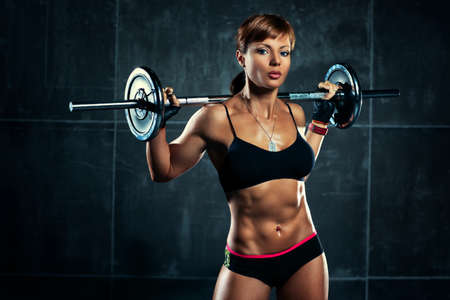 Young sports woman with barbell. Stock Photo