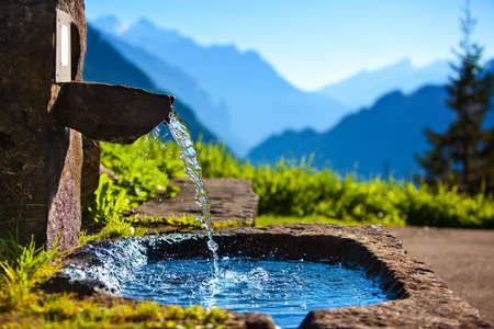 Water spring on Alps mountains background.