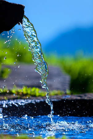 Water spring on Alps mountains background