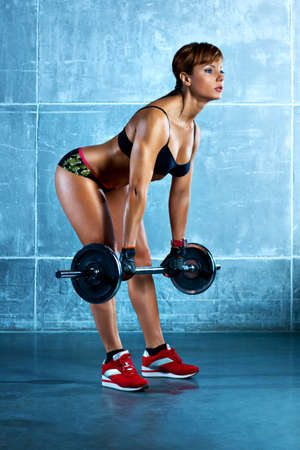 Young sports woman with barbell  Stock Photo