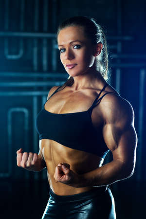 female bodybuilder: Young strong sports woman portrait
