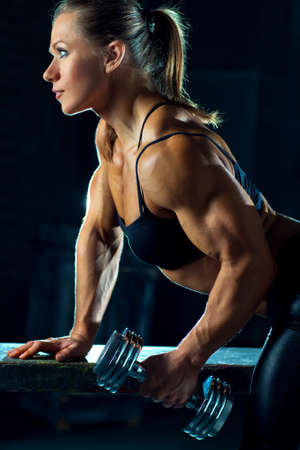 barbell: Young woman bodybuilder with dumbbell