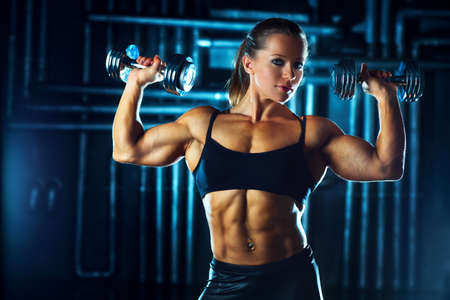 Woman bodybuilder with dumbbells on wall background