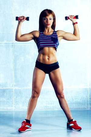 Young sports woman with dumbbells  photo