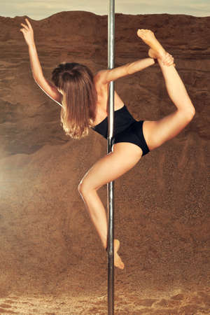 Young slim pole dance woman on sand background  photo