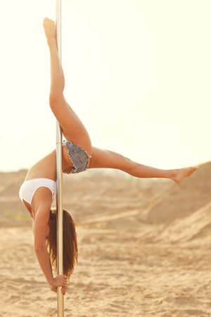 Young slim pole dance woman on sand background
