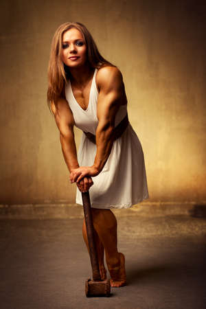 Young woman bodybuilder with hammer. Ancient style. photo