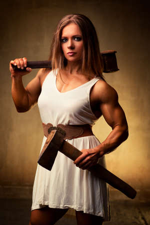 Young woman bodybuilder with hammer and axe  Ancient style  photo