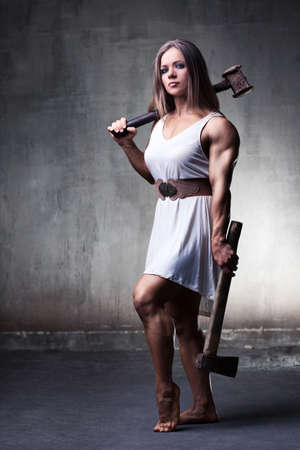 Young woman bodybuilder with hammer and axe. White colors. photo
