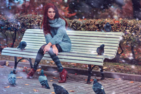 Young woman in park sitting on bench. photo