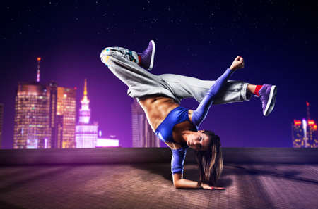 roof top: Young woman dancing on city background.