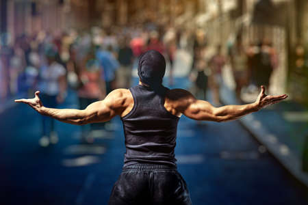 crowded street: Young strong man standing on street against people. Stock Photo