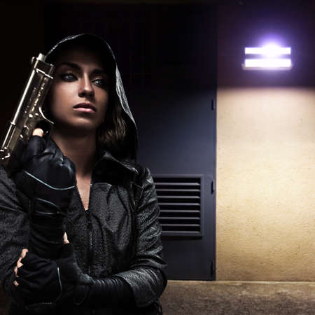 Danger woman with gun on night street. photo