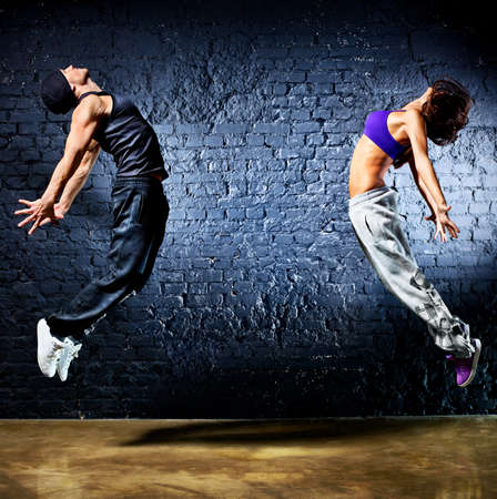 Young dancer couple jumping  On wall background