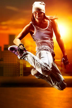hip hop girl: Young woman dancer on city background.