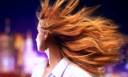 fluttering: Young woman shaking hair. On night city background. Stock Photo