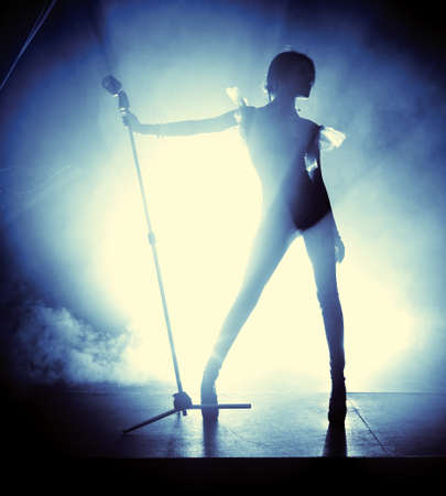 sexy woman silhouette: Young woman singer. Contrast silhouette. Stock Photo