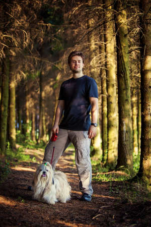 man dog: Young man and shih tzu dog portrait at forest.