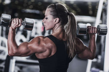 Young woman bodybuilder with dumbbells.