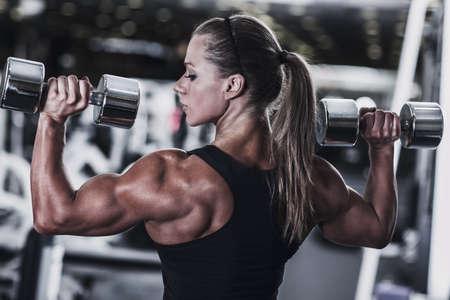 Jonge vrouw bodybuilder met halters.