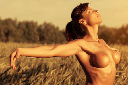 nude outdoors: Young sexy naked woman at summer field. Stock Photo