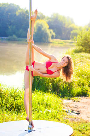 Young slim pole dance woman on nature background. photo