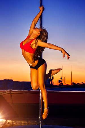 pole dance: Giovane donna sexy di ballo del palo su sfondo urbano.