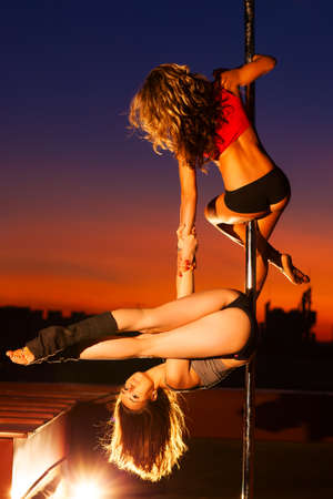 Two young pole dance women on urban background. photo