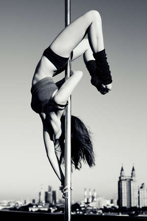 poledance: Young pole dance woman on urban background. Black and white.