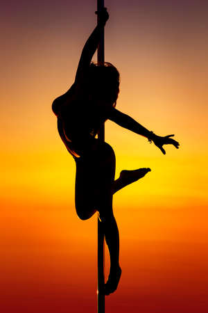 poledance: Young pole dance woman silhouette on sunset background. Stock Photo