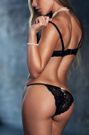 Young sexy slim woman in black lingerie and pearl jewelry. photo